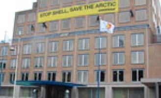 Hulpdiensten hebben handen vol aan Greenpeace demonstranten op Shell gebouw Den Haag